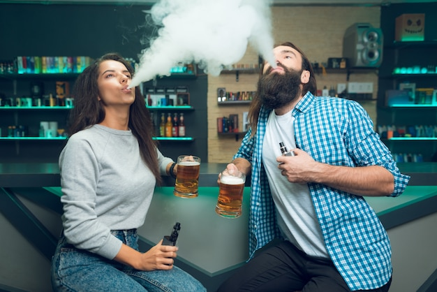 A guy and a girl are sitting with a beer in their hands. Premium Photo