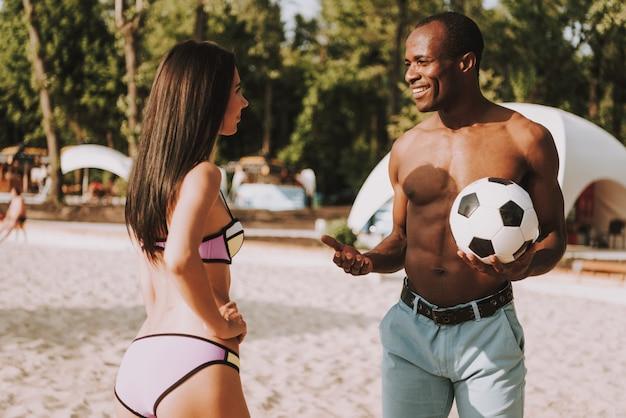 Guy and girl in bikini flirting on beach. Premium Photo
