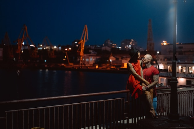 Guy and girl hugging each other on a background of the night port Free Photo
