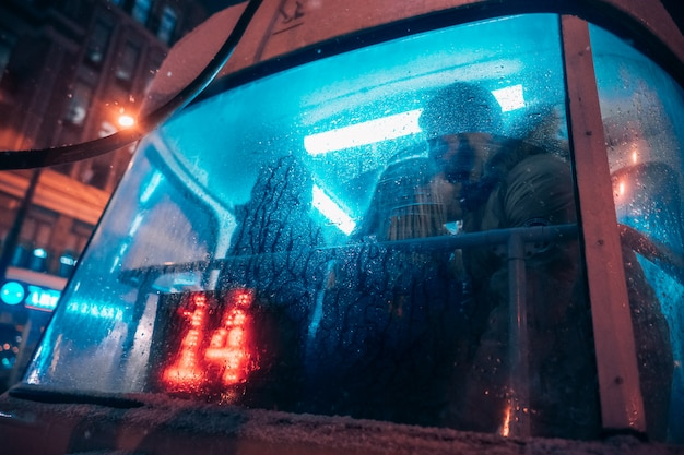 The guy and the girl kiss on the tram behind the misted glass Free Photo