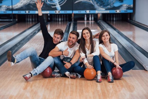 Guy si diverte con le braccia alzate. i giovani amici allegri si divertono al bowling durante i fine settimana Foto Gratuite