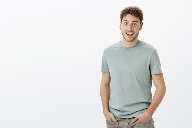 Ragazzo che sente notizie incredibili, sentendosi felice per un amico. ritratto di uomo bello dall'aspetto amichevole positivo in maglietta Foto Gratuite