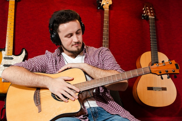 Guy holding an acoustic guitar and looking at the instrument Free Photo