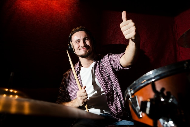 Guy holding a drumstick and giving a thumbs up Free Photo