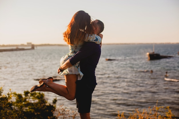 A guy holds his girlfriend in his arms on the beach in summer at sunset Premium Photo