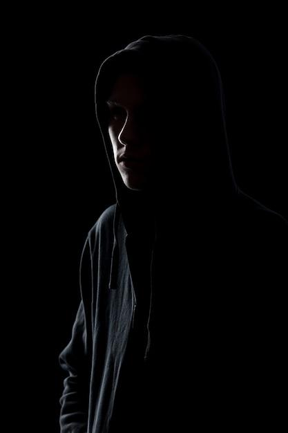 Guy in hooded sweatshirt in the dark Free Photo