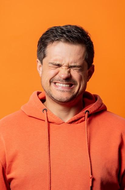 Парень в оранжевой толстовке с капюшоном недовольно щурится на оранжевый Premium Фотографии