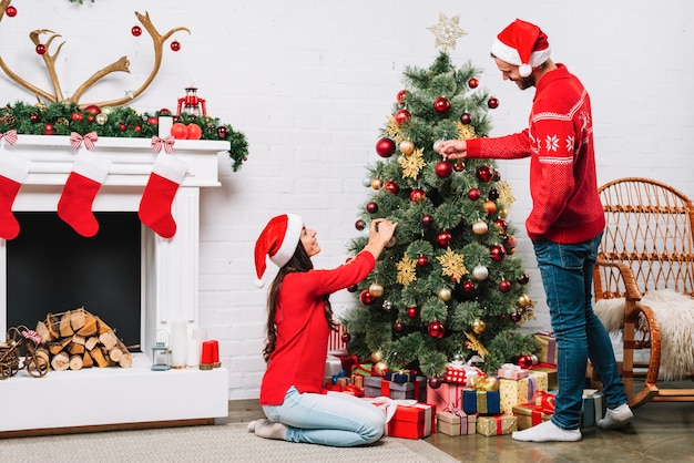 Guy And Lady Dressing Christmas Tree With Baubles Photo