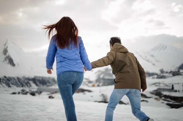 Guy leads a girl for a walk towards the snow mountains Premium Photo