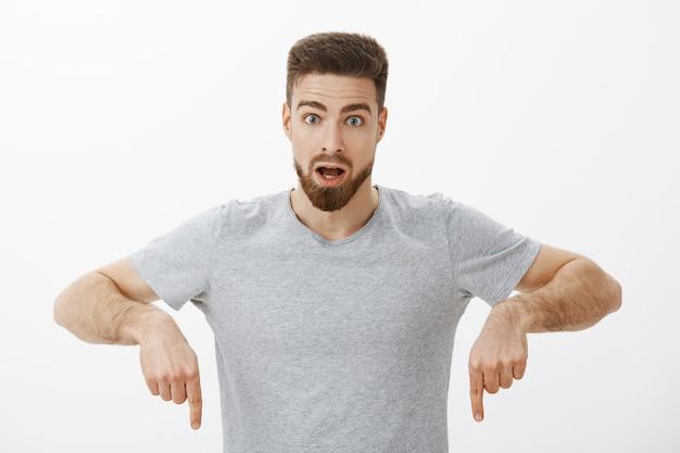 ガイはエコノミーエコノミーの仕組みを驚かせ、灰色のtシャツでポーズをとって興味をそそられ、口を開けて下向きに質問され、白い壁にびっくりしていることに驚いた 無料写真
