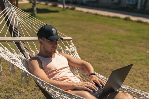 Парень лежит в гамаке с ноутбуком Premium Фотографии