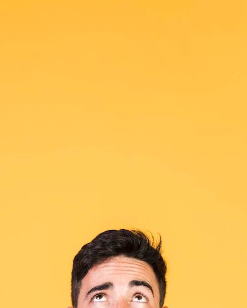 Guy looking above with copy space Premium Photo