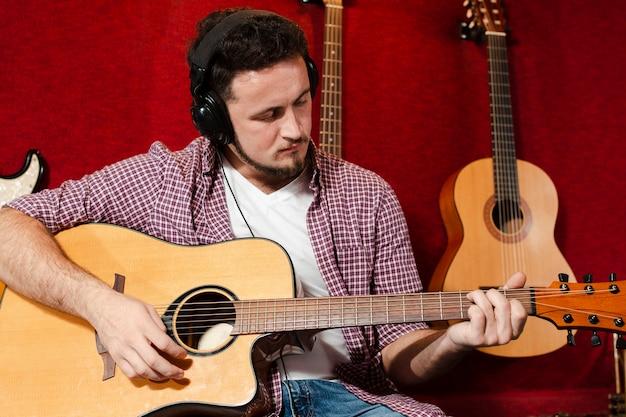 スタジオでアコースティックギターを弾く男 無料写真
