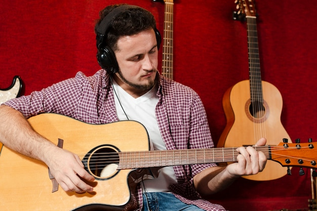 Guy playing acoustic guitar in the studio Free Photo