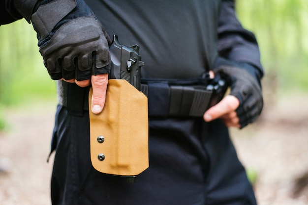 The guy puts the gun in the holster close-up Premium Photo