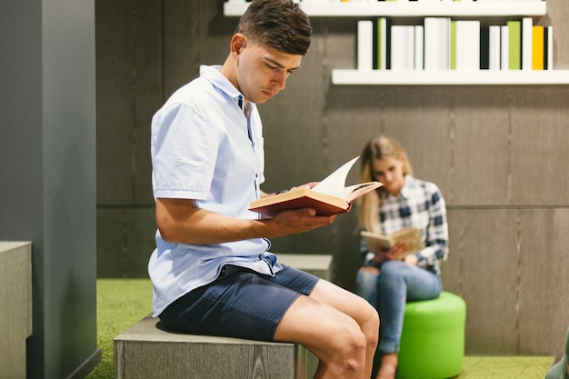 Guy reading book in modern library Free Photo