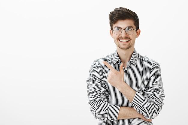 Парень вспомнил забавный момент. портрет заинтересованного симпатичного европейца-фрилансера в очках, указывая в левый верхний угол и широко улыбаясь, думая о шутке, стоящего над серой стеной Бесплатные Фотографии