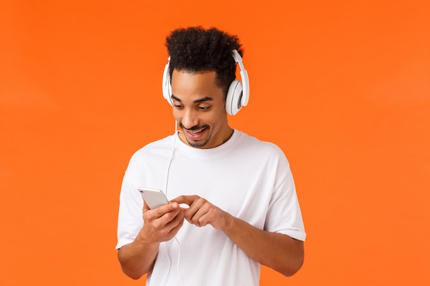 右のトラックを検索する男は気分を後押しします。白いtシャツでうれしそうな魅力的なアフリカ系アメリカ人男性、ヘッドフォンをつけて、笑顔のスマートフォンでプレイリストを閲覧、音楽を聴く、オレンジ Premium写真