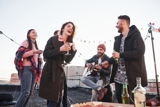 Guy sing funny song. cheerful young people smiling and drinking at the rooftop. pizza and alcohol on the table. guitar player Free Photo