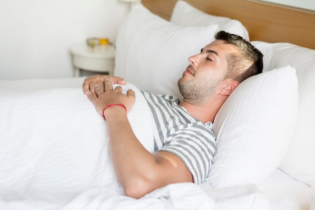 Guy sleeping with hands on his chest Free Photo