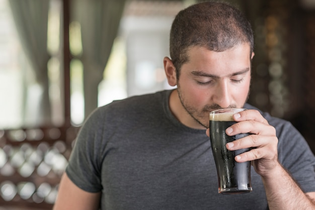 Guy smelling beer in pub Free Photo