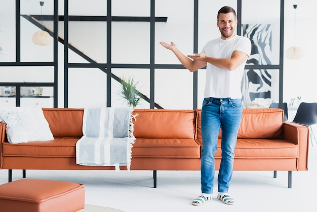 Guy standing and showing his living room Free Photo