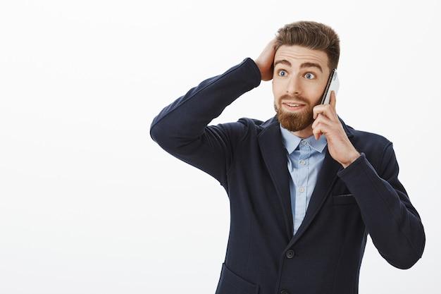 立っている男は驚嘆の申し出を受けて気絶しました。携帯電話を介して話している散髪に触れるスタイリッシュなフォーマルスーツで驚いて喜んで言葉のない白人男性起業家の肖像画 無料写真
