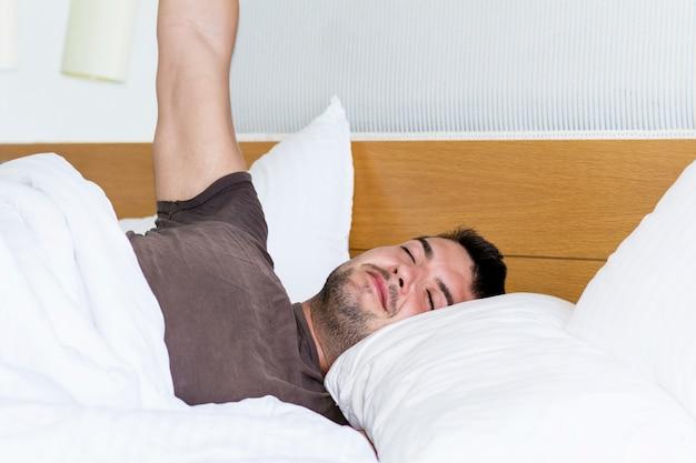 Guy si estende a letto dopo il risveglio Foto Gratuite