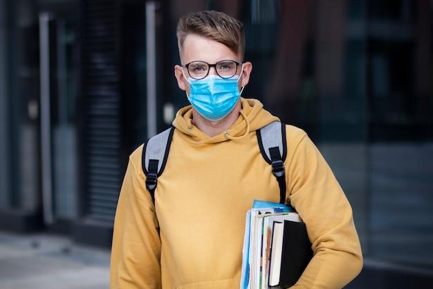 男の学生、生徒の少年、保護用の医療マスクと顔の本の屋外大学のメガネの若い男 Premium写真