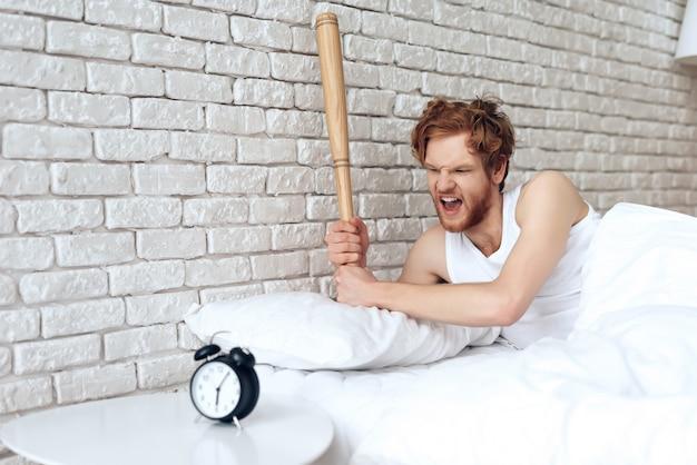 Guy swung the baseball bat on the alarm clock Premium Photo