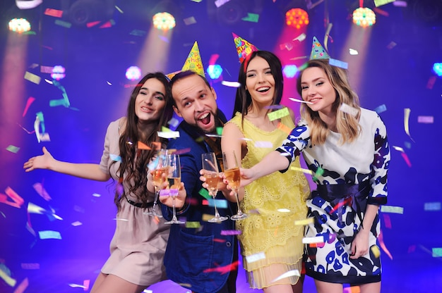A guy and three girls rejoice and celebrate the party in the night club Premium Photo