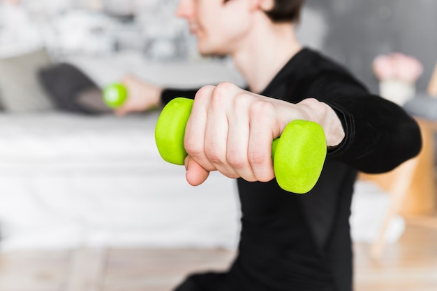 Guy training and lifting green dumbbells Free Photo