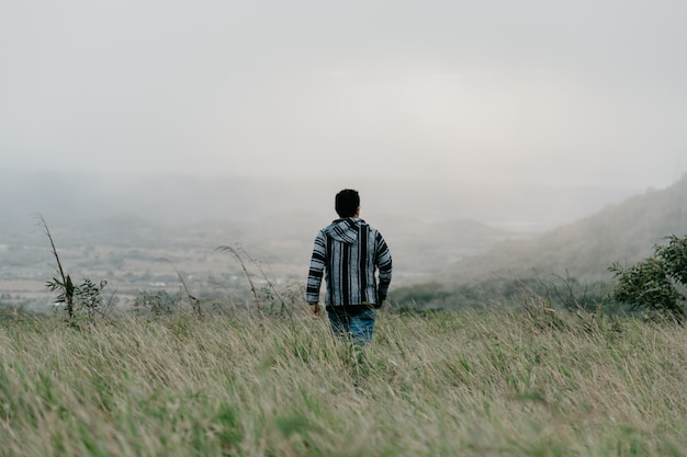 A guy walking in the field through grass on a gloomy foggy day Free Photo
