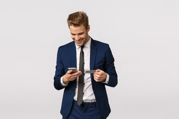 Guy want buy flowers for girlfriend, working office, holding smartphone and credit card, smiling ad enter billing details display, standing white background. businessman paying for purchase Premium Photo