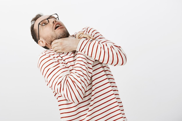 Guy wants kill himself not to listen boring stories anymore. portrait of funny european man in glasses, holding hands on neck and bending backwards Free Photo