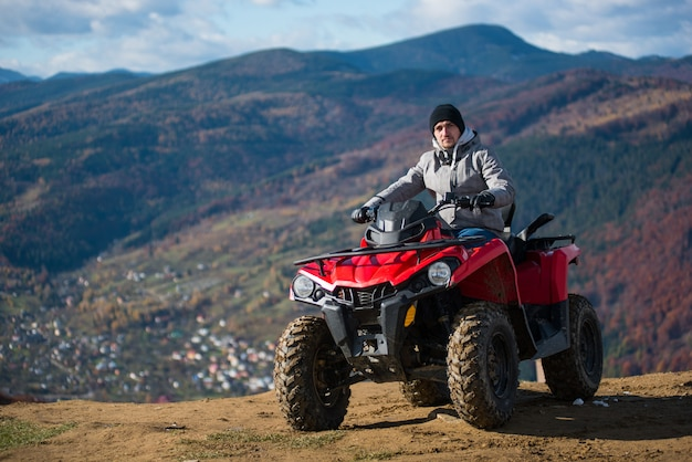 Guy in winter clothes on a red quad bike on a mountain top looking at the camera Premium Photo