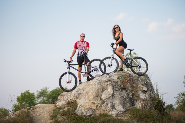 Guy with bicycle with pretty fitness girl on a mountain bike standing on a rock Premium Photo