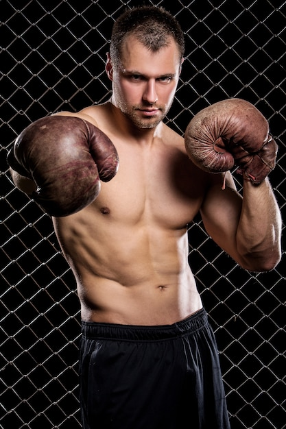 Guy with a boxing gloves showing muscles on fence Free Photo