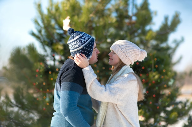 Guy with a girl kiss on a background of green christmas tree decorated with festive toys and garlands in the winter in the forest Premium Photo