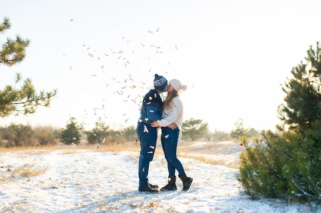 The guy with the girl kiss in the winter in the woods against the  of falling candy. Premium Photo