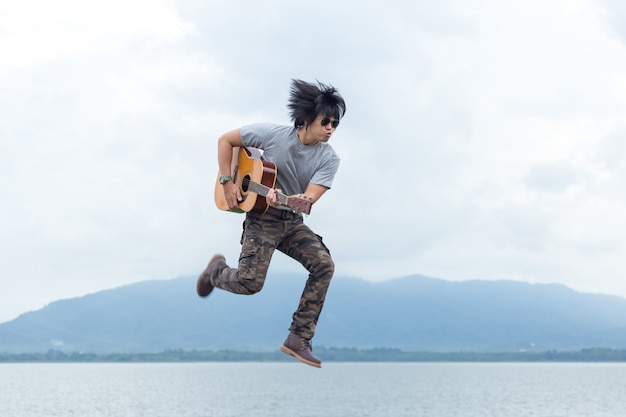 Guy with guitar standing on the dam Premium Photo