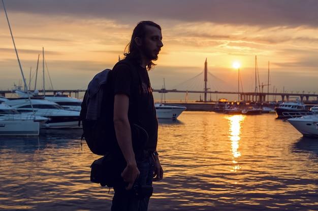 Парень с длинными волосами в силуэте стоит на пляже с фотоаппаратом, где яхты пришвартованы к пристани на закате летом, вдали вантовый мост Premium Фотографии