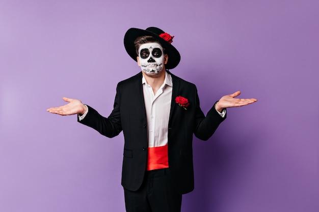 Ragazzo con la maschera del teschio allarga le mani, non potendo in alcun modo aiutare. ritratto di uomo incredulo in posa su sfondo isolato. Foto Gratuite