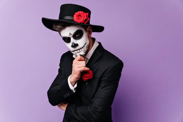 仮面舞踏会の顔を塗った男がしんみりと顎に触れ、真剣にカメラを覗き込む。 無料写真