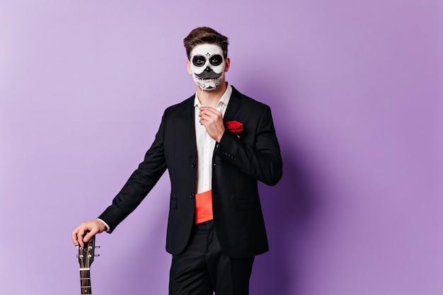 ギターに寄りかかって、偽の口ひげでポーズをとる古典的なスーツの顔を描いた男。 無料写真