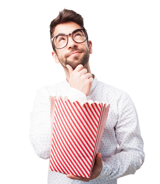 Guy with popcorn thinking about the film Free Photo