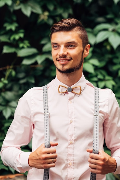 Guy with wooden bow tie and suspenders smiles against the background of green leaves Premium Photo