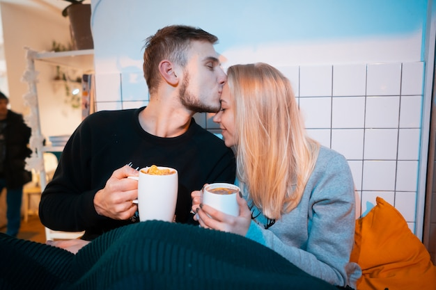 Guy with a young woman drinking hot coffee and tea Free Photo