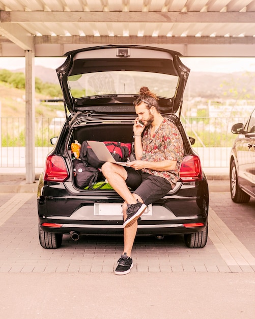 Guy working on laptop in trunk Free Photo