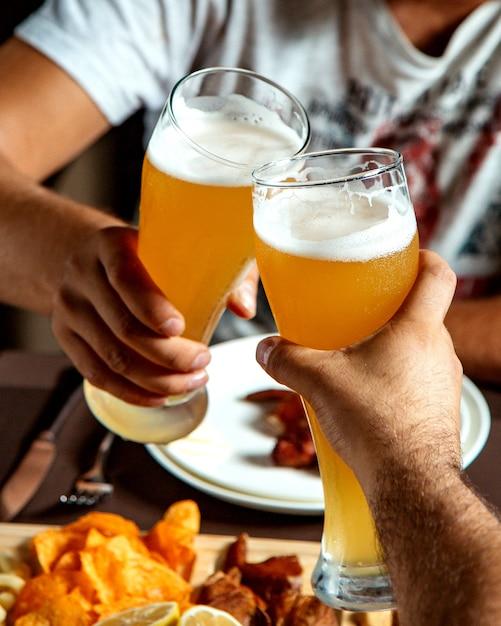 Ребята пьют пиво со смешанными закусками Бесплатные Фотографии
